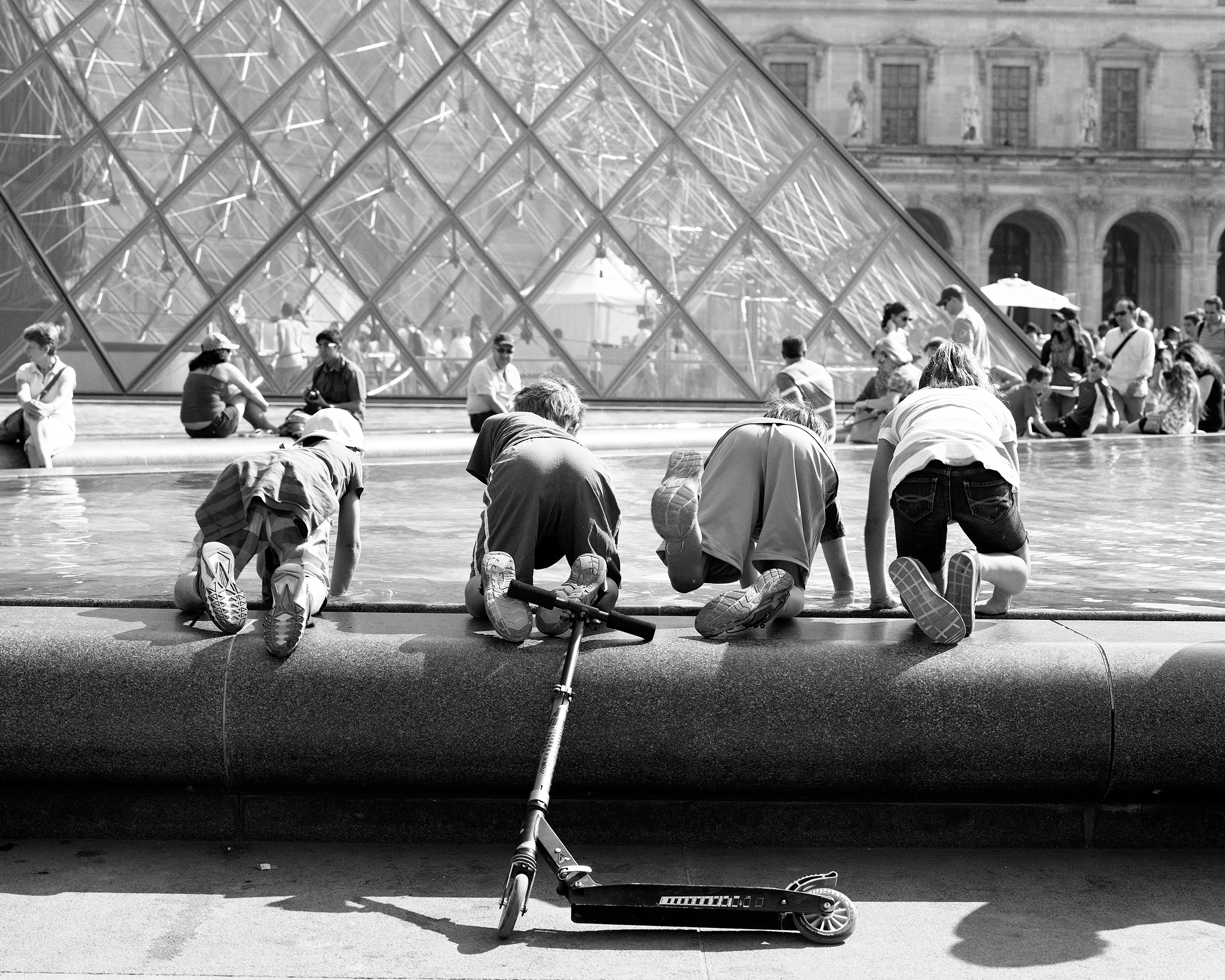 louvre museum               paris france black and white film street photography children               scooter art people youth fountain pyramid